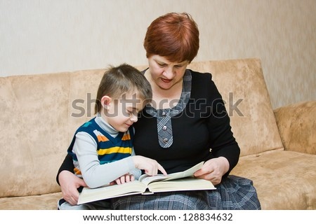 a grandmother reads a book to the grandchild