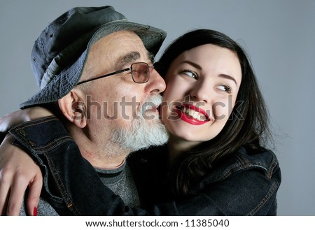 a grandpa is kissing his granddaughter and she is smiling - stock photo