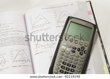 a graphing or scientific calculator resting on a calculus math book - stock photo