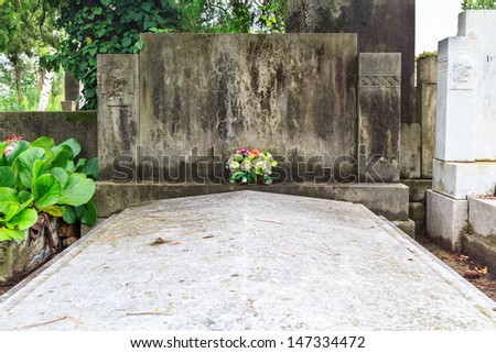 A grave without inscription but flowers - stock photo