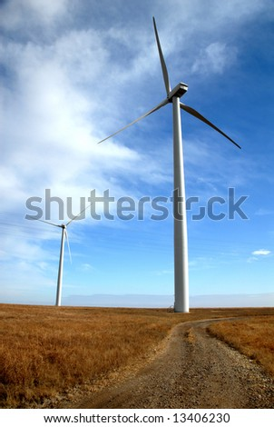 A gravel road leading up to a large turbine at from a Kansas Wind Farm.