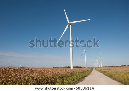 A gravel road leads past wind turbines and a corn field in rural Indiana