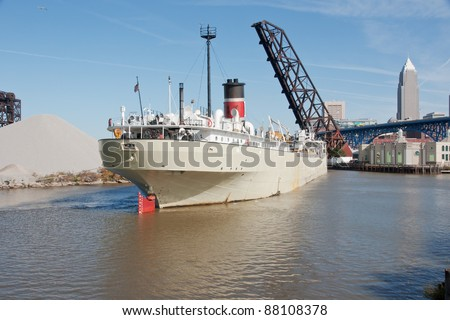 A Great Lakes bulk freighter on the Cuyahoga River in Cleveland, Ohio with a bascule style bridge, a nightclub, a pile of aggregate, and a skyscraper in the background - stock photo
