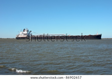 A Great Lakes self-unloading bulk carrier ship navigates the waters inside the Lake Erie break wall heading to the Cleveland Bulk Terminal dock