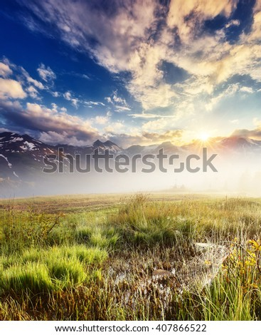 A great view of the foggy field and green grass glowing by sunlight. Dramatic and picturesque morning scene. Location place: High Alpine Road, Austria. Europe. Beauty world. Warm toning effect.