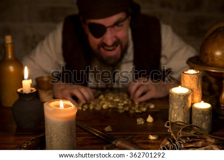 a greedy Pirate with a treasure of gold behind a lot of candles - stock photo