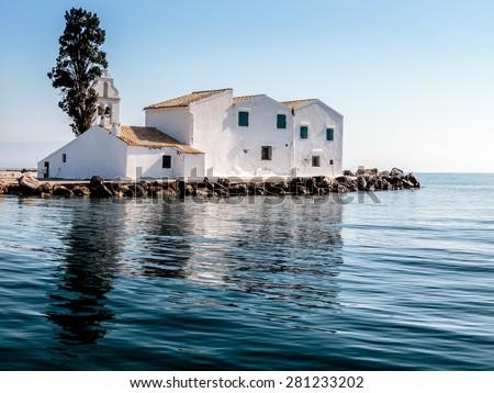 A Greek orthodox monastery of Vlacherna on an island in shallow sea near Corfu Town, connected by bridge to mainland - stock photo