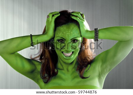 A green alien or Martian woman posing over a silver brushed metal backdrop. - stock photo
