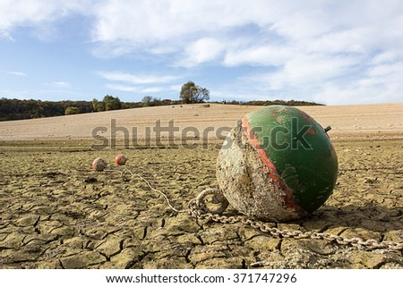 a green anchor buoy on a dry lake - stock photo