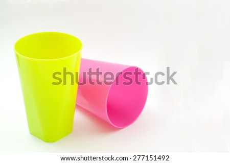 A green and pink plastic cups isolated on white background  - stock photo