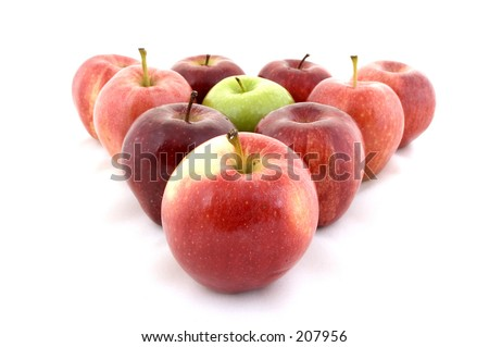 A green apple in a triangle of red apples - stock photo