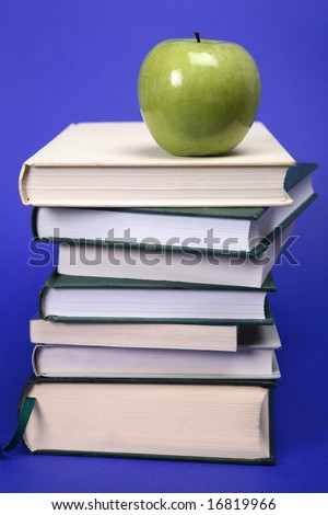 A green apple on a pile of books with a blue background