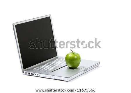 A green apple sitting on a laptop isolated - stock photo