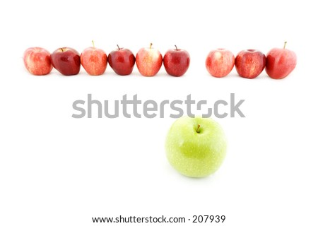 A green apple stands out from a line of red apples - stock photo