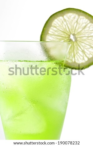 A green beverage in a glass with a slice of lime. - stock photo