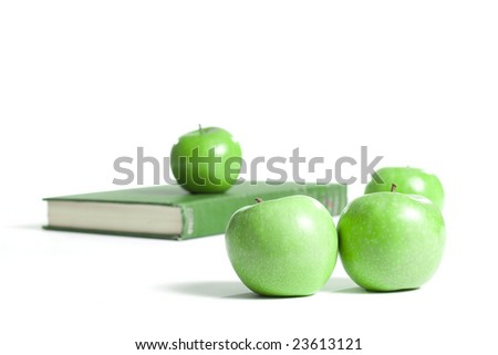 A green book isolated on white with green apples around it.