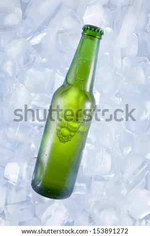A green bottle of beer on ice. - stock photo