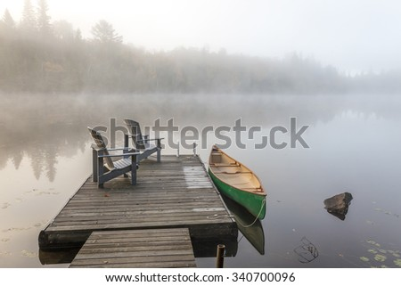 A green canoe tied to a wooden dock with a pair of empty Adirondack chairs - Haliburton Highlands, Ontario, Canada - stock photo