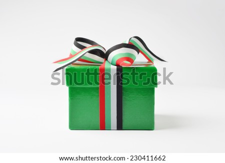 A green color gift box wrapped with UAE flag color ribbon. - stock photo
