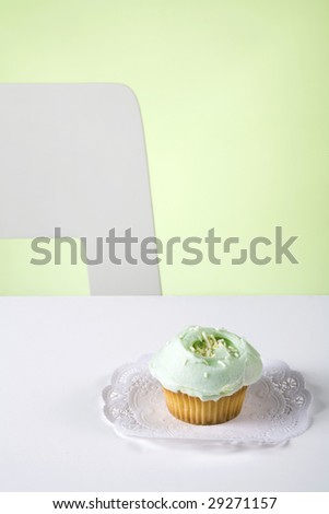 A green cupcake on a table against a green background. - stock photo
