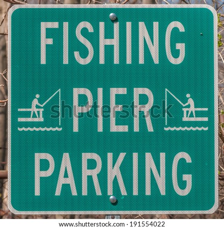 A green Fishing Parking Sign giving instructions on parking. - stock photo