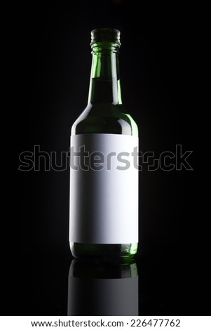A green glass bottle with liquor with blank label reflective bottom isolated black.