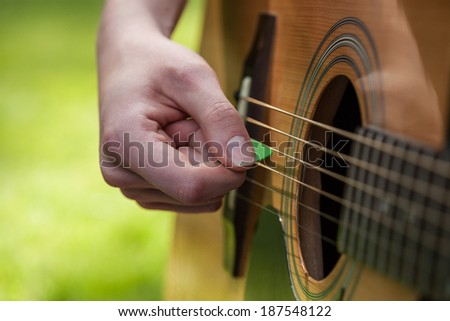 A green guitar pick in a musician's hand - stock photo