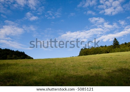 a green highland with blue sky and cloud