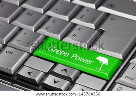 A green key on a keyboard saying 'Green Power' and showing a tree. Using green power at home or in the company - stock photo
