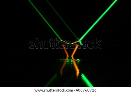 A green laser beam reflection in different colored glass. - stock photo