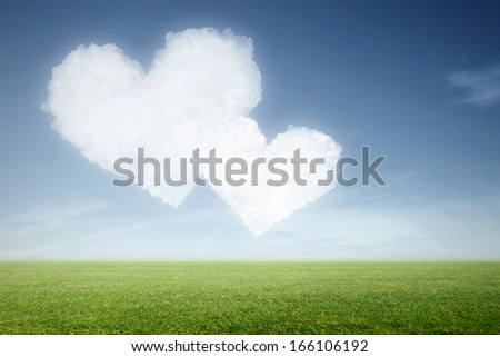 a green meadow with clouds in heart shape in the sky - stock photo