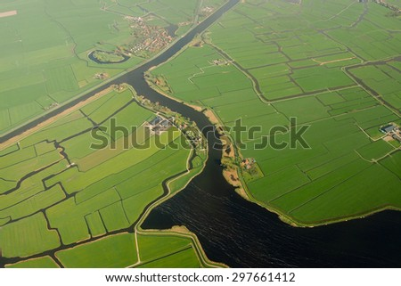 A green rice field with canal on top view  - stock photo