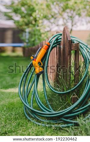 a green rubber garden hose with nozzle outdoor - stock photo