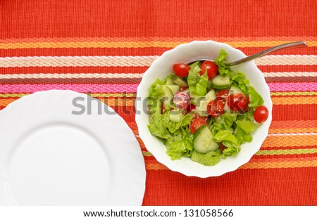 A green salad in a stylish white bowl. With rocket leaves cherry tomatoes spanish onions and capsicum. Empty white plate near. - stock photo