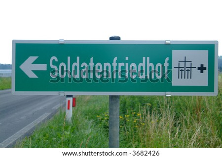a green sign with a white script military cemetery - stock photo