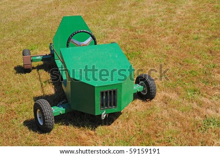 A green soapbox racing car displayed on the grass. - stock photo