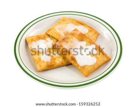A green striped plate with three freshly cooked toaster pastries iced with cream cheese frosting on a white background. - stock photo