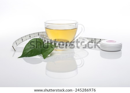 A green tea, cup and white tape measure, leaf(leaves) isolated white at the studio. - stock photo