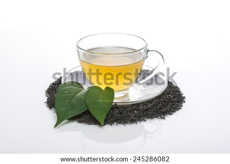 A green tea green leaf(leaves), glass cup isolated white at the studio. - stock photo