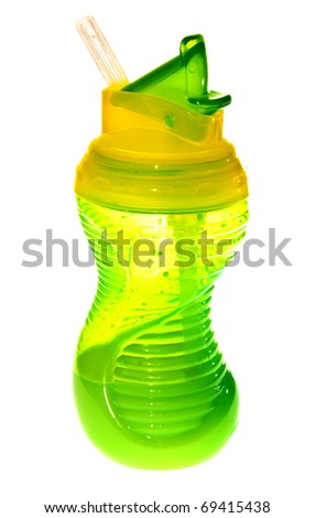 A green translucent childrens cup with milk on a white background