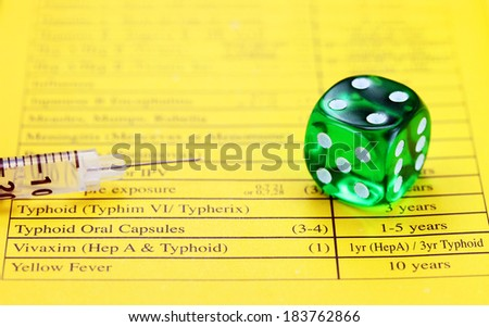 A green translucent dice, placed on a vaccination passport with a loaded syringe adjacent to it, asking the question, are your vaccinations up to date. - stock photo