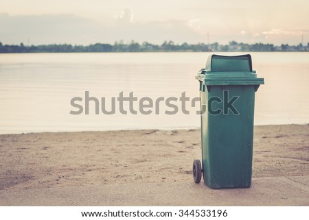A green trash bin on the beach - stock photo