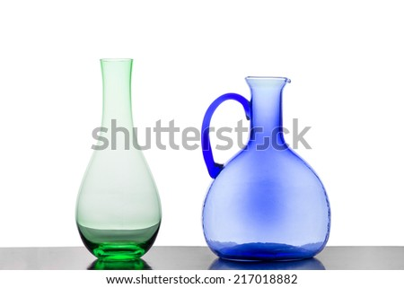 A Green Vase and a Blue Jug Against a White Background - stock photo