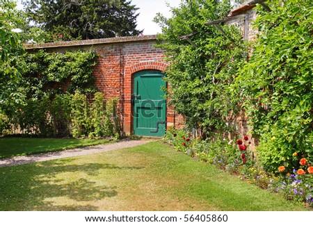A Green wooden door through an English Walled garden - stock photo