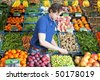 A greengrocer at work amidst various crates of fresh fruit and vegetables in a shop - stock photo