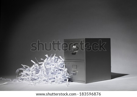 A grey filing cabinet in a spotlight next to a small pile of shredded paper. - stock photo