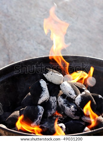 A grill with charcoal and flames - stock photo