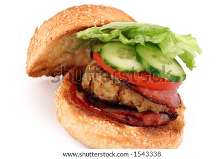 A grilled chicked pattie, bacon and fresh salad on a toasted sesame seed roll isolated - stock photo