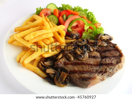 A grilled ribeye steak served with mushrooms,  chips (french fries) and a garden salad of lettuce, cucumber, baby carrot and capsicum - stock photo
