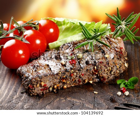 A grilled serving of succulent tender peppered steak garnished with lettuce, tomato and fresh rosemary herbs - stock photo